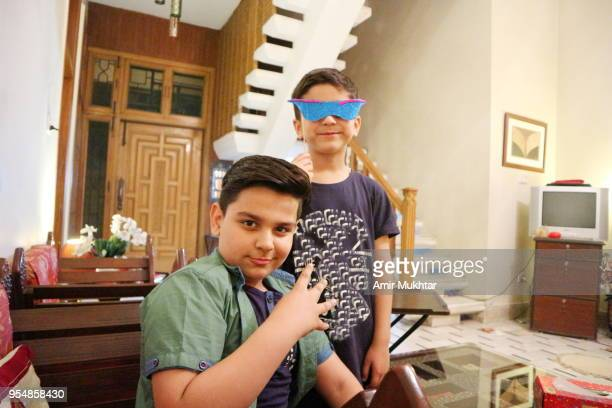 young boys having fun in a party with face mask on - cute pakistani boys stock photos and pictures