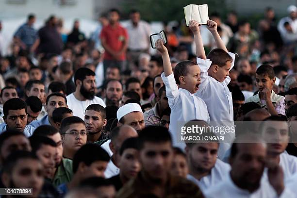 Young boys hold up copies of the Koran as they listen to a speech by Hamas leader in the Gaza Strip Ismail Haniya during a mass prayer event in the...