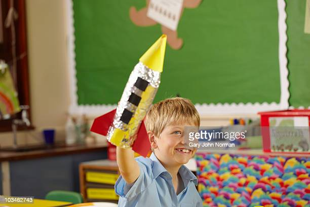 Young boys holds rocket