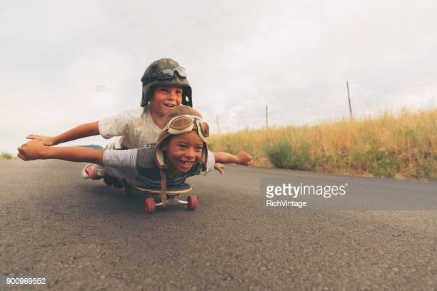 young boys imagine flying on skateboard - coraggio foto e immagini stock