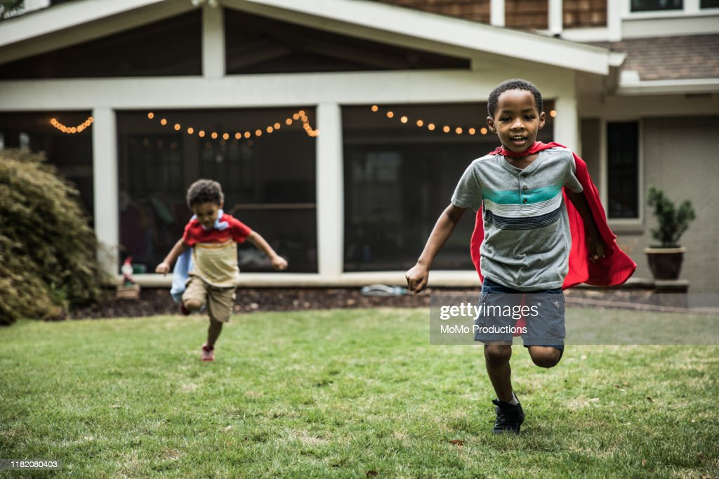 Young boys (3 yrs and 6yrs) in capes playing in backyard : Stock Photo