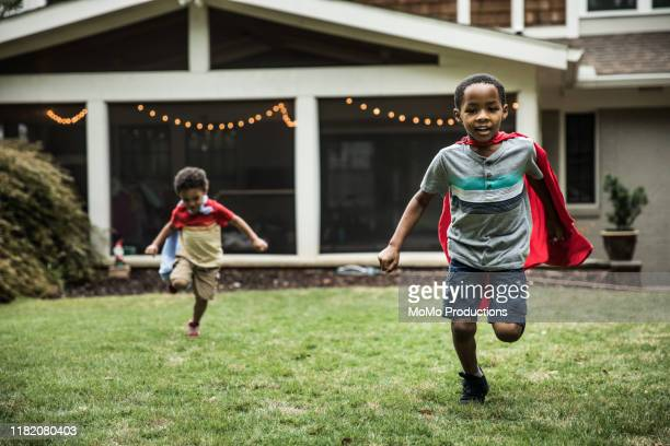 young boys (3 yrs and 6yrs) in capes playing in backyard - playing stock-fotos und bilder