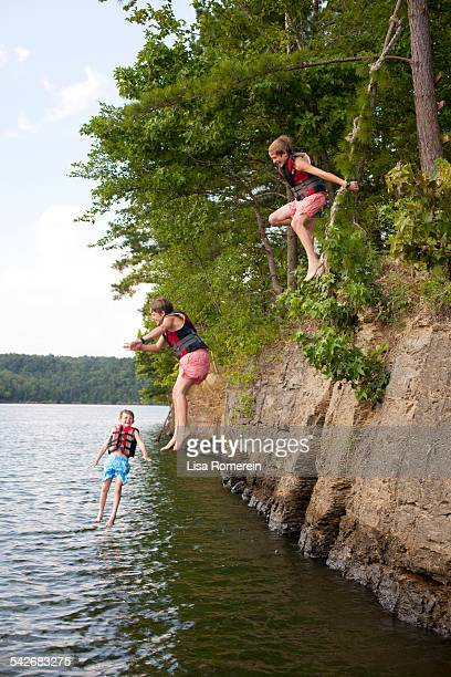Young boys in jumping off of cliff into lake