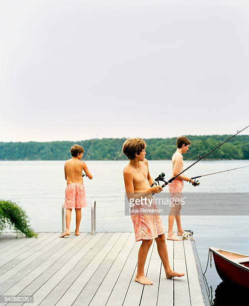 Young boys in shorts fishing on dock next to canoe