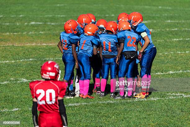 Young boys in the huddle during a Pop Warner football game