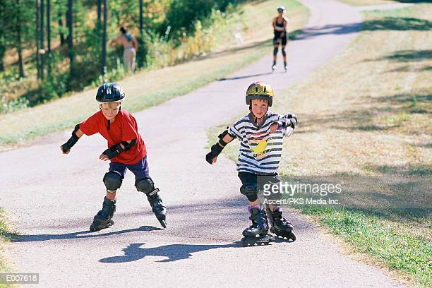 Young boys inline skating on path