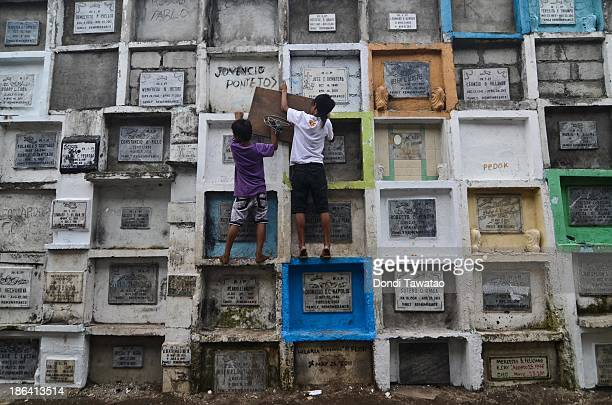 Young boys install a makeshift basketball board at a public cemetery ahead of All Saints' Day on October 31 2013 in Manila Philippines As the largest...