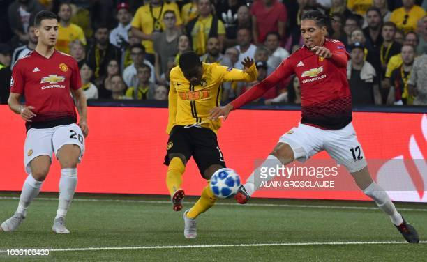 Young Boys Ivorian forward Roger Assalé shoots past Manchester United's English defender Chris Smalling and Manchester United's Portuguese defender...