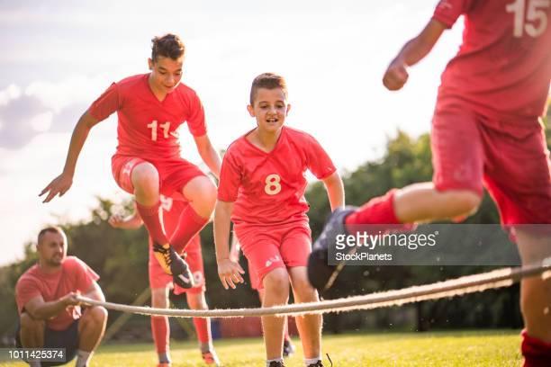 junge burschen, die einen sprung über ein seil im park - jugendmannschaft stock-fotos und bilder