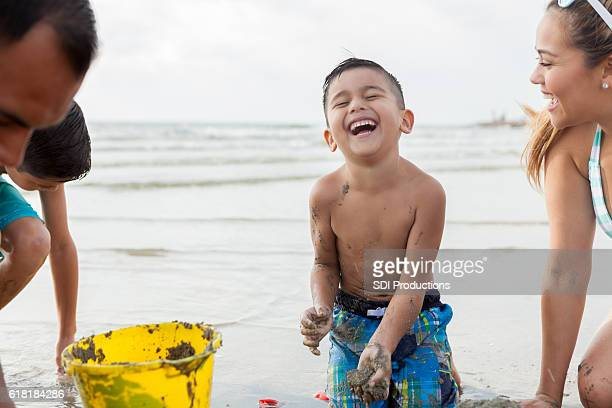 young boys laughs while playing in the sand - galveston stock pictures, royalty-free photos & images