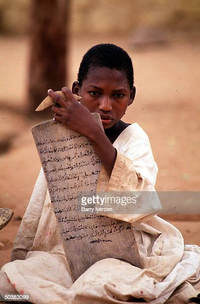 Young boys learning the Koran by reciting and memorizing off of wooden tablets inscribed with Koranic versses