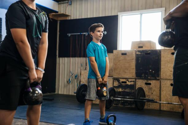 Young boys lifting kettlebells at gym