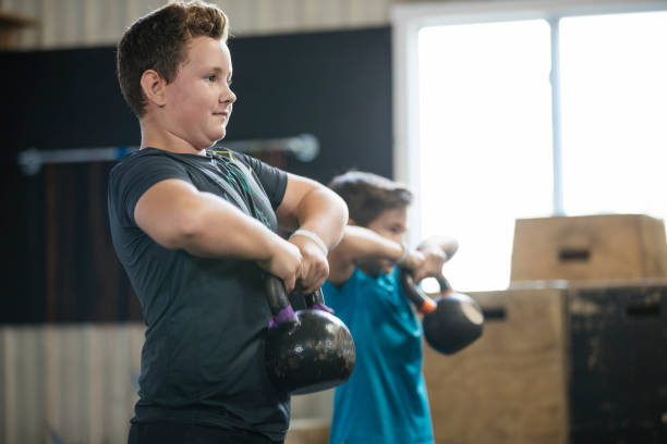 Young boys lifting kettlebells at gym