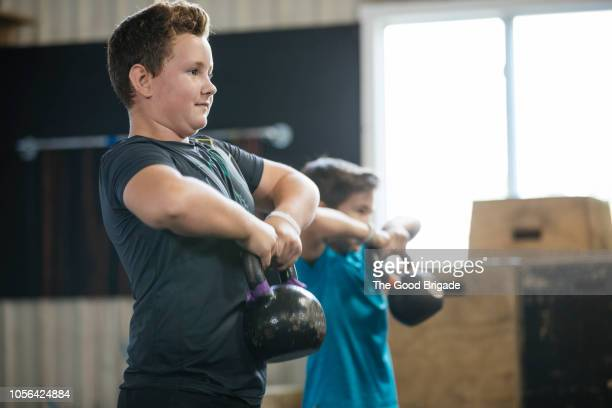 young boys lifting kettlebells at gym - kids weightlifting ストックフォトと画像