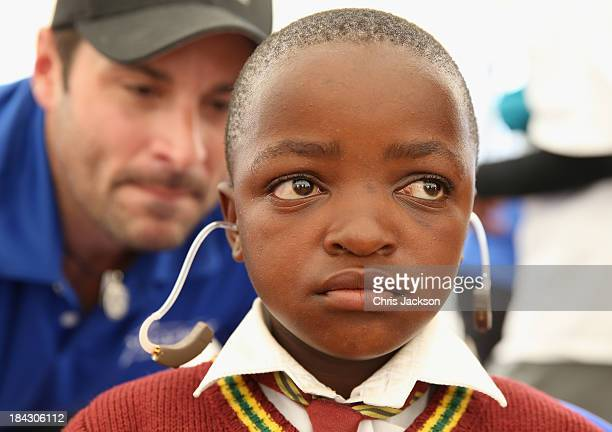 Young boys listens to see if he can hear as a Starkey volunteer talks into his ear as he has hearing aids fitted at Lesotho Cooperative College on...