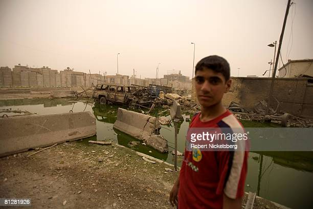 Young boys living in Sadr City at a concrete wall recently erected by American forces look over destroyed and burned vehicles from heavy fighting...