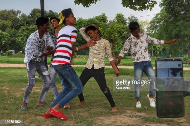 Young boys make videos for TIKTOK in a park in New Delhi India on 4 August 2019