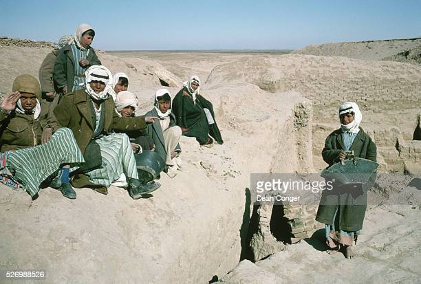 Young boys pause from working on an excavation team at the ruins of the ancient Mesopotamian city of Mari Syria | Location Mari Syria
