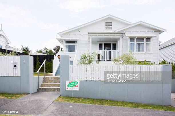 Young boys peaks around gate in front of villa with Sold sign