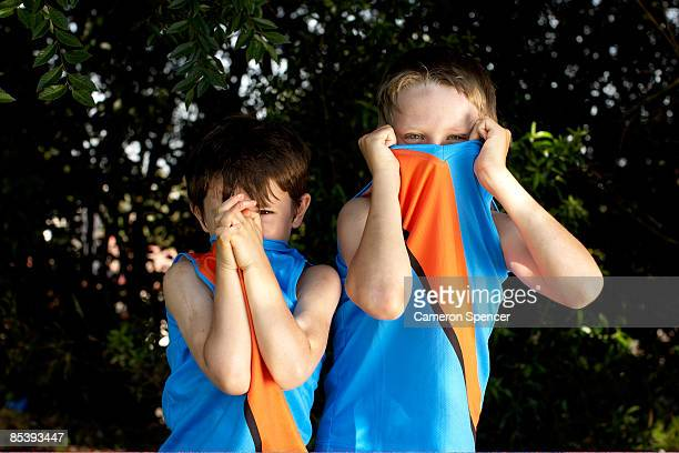 young boys peeping over their football jumpers - cameron young stock photos and pictures