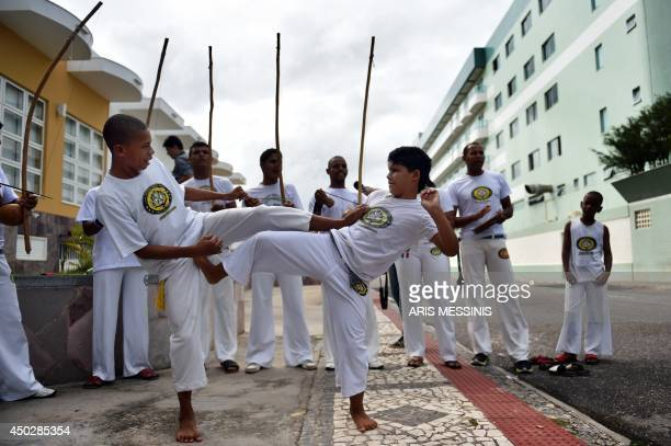 Young boys perform the Brazilian martial art of Capoeira as they await the arrival of the Greek football team at the their hotel in Aracaju on June 8...
