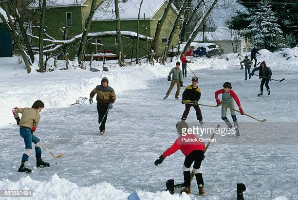Young boys play a game of ice hockey outdoors on the ice