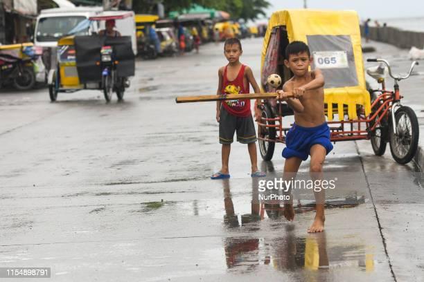 Young boys play a street baseball near the Pasig River in Baseco Compound in Manila The Batangas Shipping and Engineering Company Compound is the...
