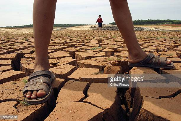 Young boys play at the bottom of a cracked dried reservoir on June 2 2005 in Leizhou of western Guangdong Province southern China According to...