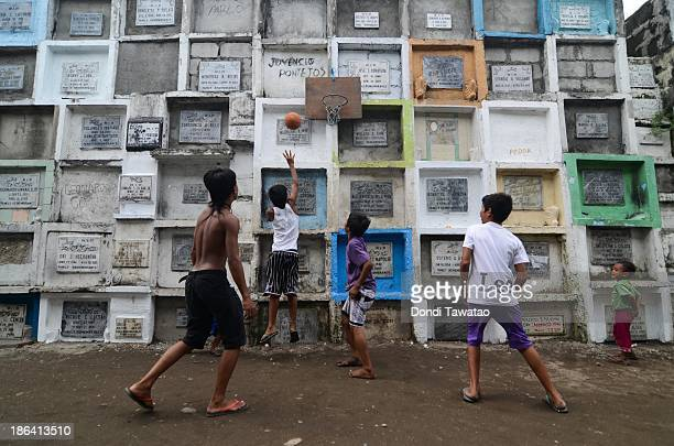 Young boys play basketball at a public cemetery ahead of All Saints' Day on October 31 2013 in Manila Philippines As the largest Catholic nation in...