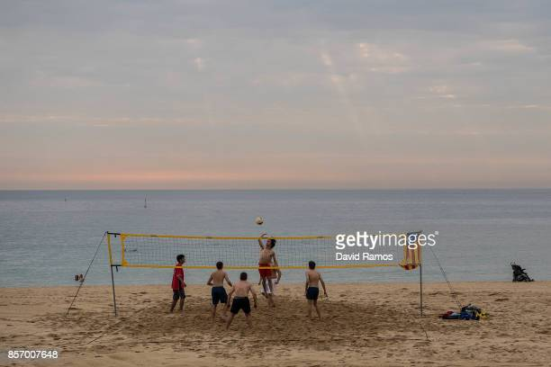 Young boys play beach volley ball with a Catalan Proindependence flag known as 'Estelada' tied to the net as a regional general strike to protest...