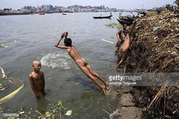 Young boys play in the Buriganga river in Sadarghat in Dhaka Bangladesh on May 3 2006 Dhaka is the fastest growing city in Asia with a population of...