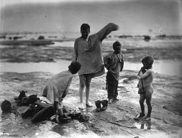 Young boys play on a beach in Whitby, Yorkshire.An...