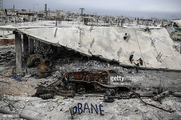 "Young boys play on a destroyed building near a sign reading ""Kobane"" in the Syrian town of Kobane, also known as Ain al-Arab, on March 28, 2015...."