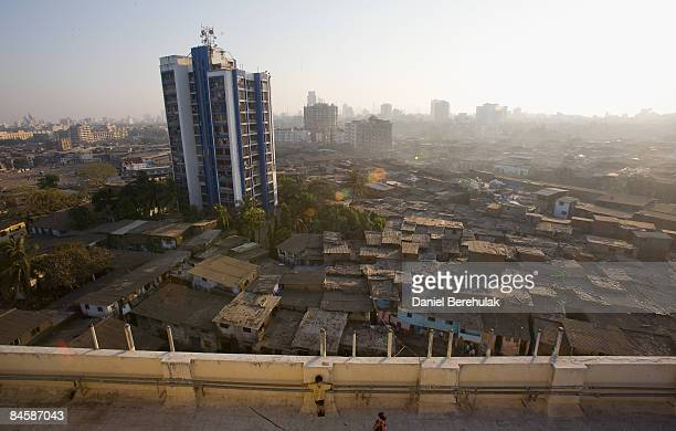 Young boys play on the roof of a building as the Dharavi slum sprawls into the distance on February 2 2009 in Mumbai India The redevelopment of...