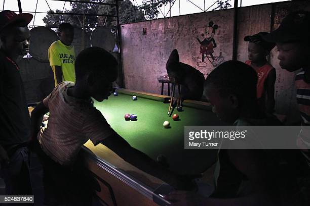 Young boys play pool by torchlight in the gathering darkness because electricity is only available for a few hours usually late at night in...