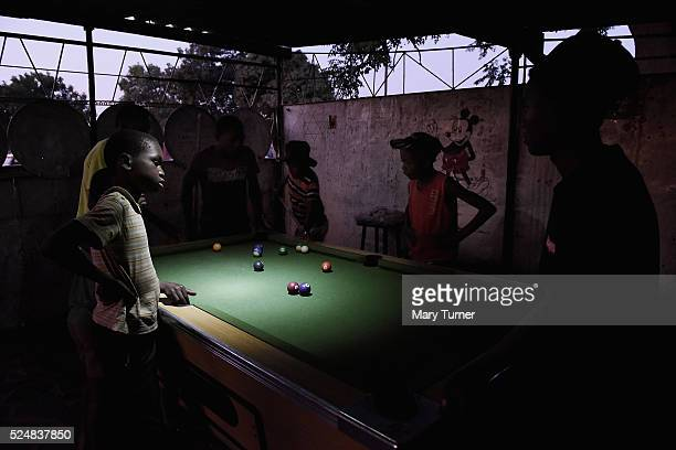 Young boys play pool by torchlight in the gathering darkness in the town of Chitungwiza where electricity is only provided for a few hours usually...