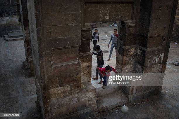 Young boys play soccer outside a mosque in the poor neighbourhood of the 'City of the Dead' on December 14 2016 in Cairo Egypt The 'City of the Dead'...