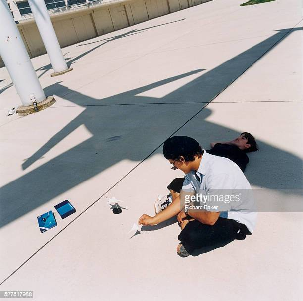 Young boys play with supersonic Air France Concorde models beneath the shadow of a fighter jet at the Le Bourget airport days after the crash at...