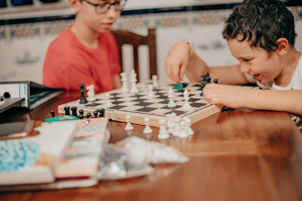 young boys playing chess at home,side view