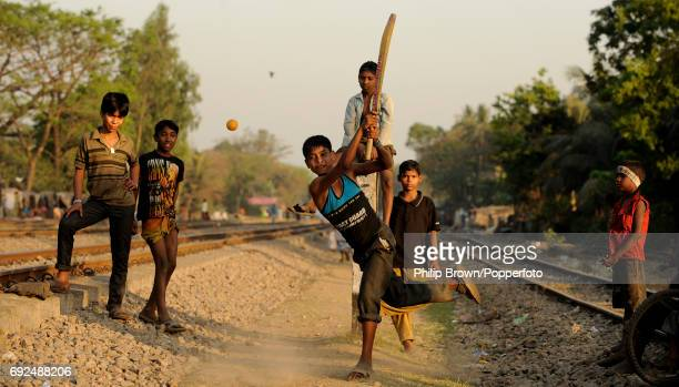 Young boys playing cricket between railway lines at Chittagong in Bangladesh on 8th March 2011