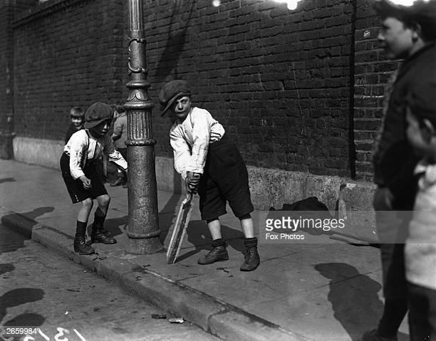 Young boys playing cricket in a street in London's East End