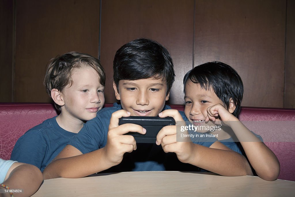 Young boys playing games with smartphone : Stock Photo