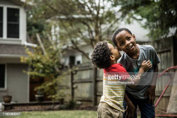 young boys (3 yrs and 6yrs) playing in backyard - whispering stock pictures, royalty-free photos & images