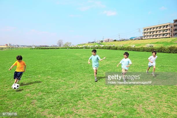 Young boys playing soccer on field. Futako-tamagawa, Setagaya-ku, Tokyo Prefecture, Japan