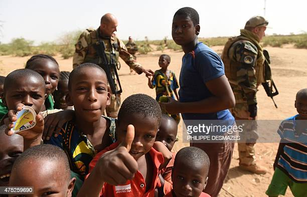 Young boys pose near French soldiers of Operation Barkhane an antiterrorist operation in the Sahel patrolling in Gao northern Mali on May 30 2015...