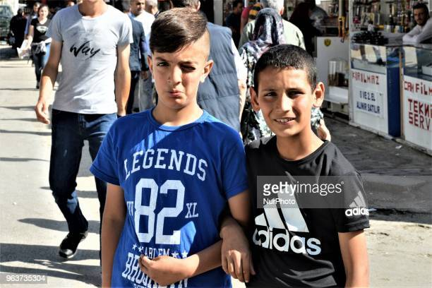 Young boys posing for a photo walk around a bazaar during the Muslim holy fasting month of Ramadan in the historic Ulus district of Ankara Turkey on...
