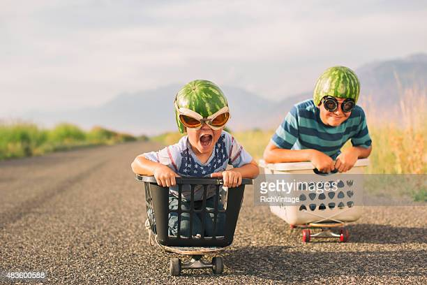 young boys racing wearing watermelon helmets - rivaliteit stockfoto's en -beelden