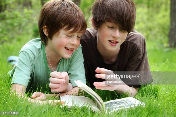 Young boys read a book outside
