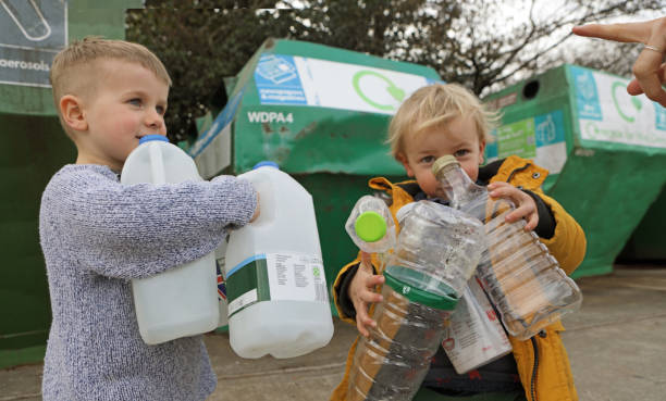 Young boys recycling plastic bottles