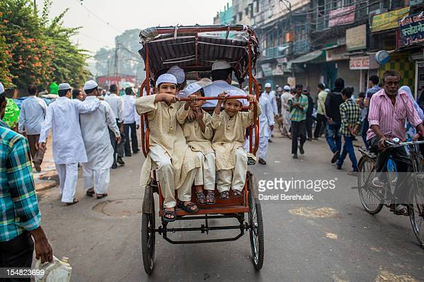 Young boys ride on the back of a rickshaw after Eid alAdha prayers at Jama Masjid on October 27 2012 in New Delhi India Eid alAdha also known as the...